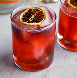 overhead view of a pink blackberry cocktail with vodka and elderflower topped with a dehydrated lemon wheel