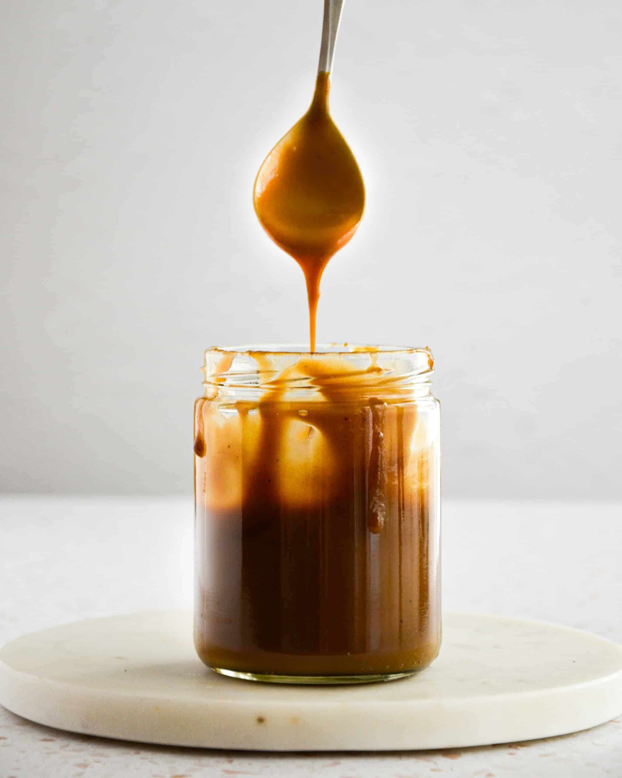 drizzling vegan salted caramel from a spoon into a mason jar