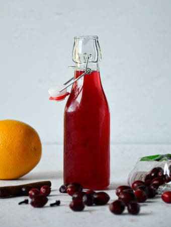 Spiced-Orange-Cranberry-Simple-Syrup-in-Jar-Straight-On-with-Props