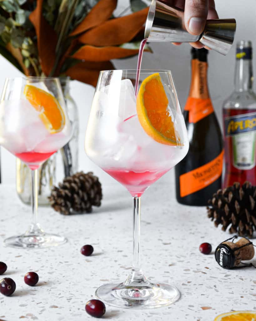 Spiced Orange & Cranberry Winter Aperol Spritz - pouring simple syrup