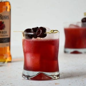 pink drink with three cherries on top and bottle of bourbon on the left side