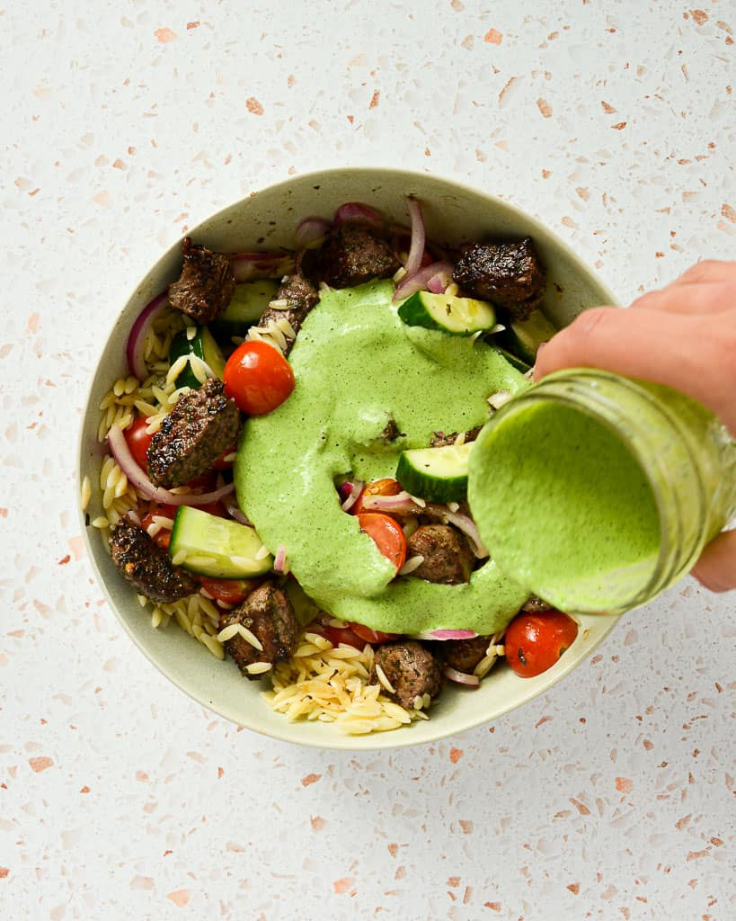 Pouring Lemon Mint Yogurt Dressing on Protein-Packed Greek Pasta Salad
