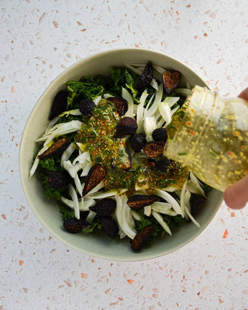 pouring lemon chive dressing on kale fennel dried fig salad