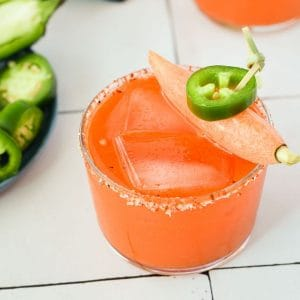 carrot juice margarita in a small glass topped with a carrot and a jalapeño slice