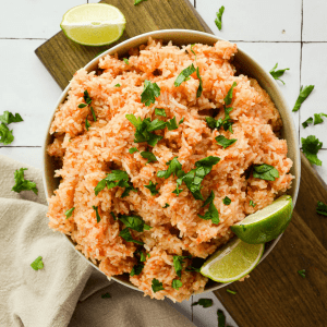 bowl of vegan mexican rice topped with lime wedges and cilantro