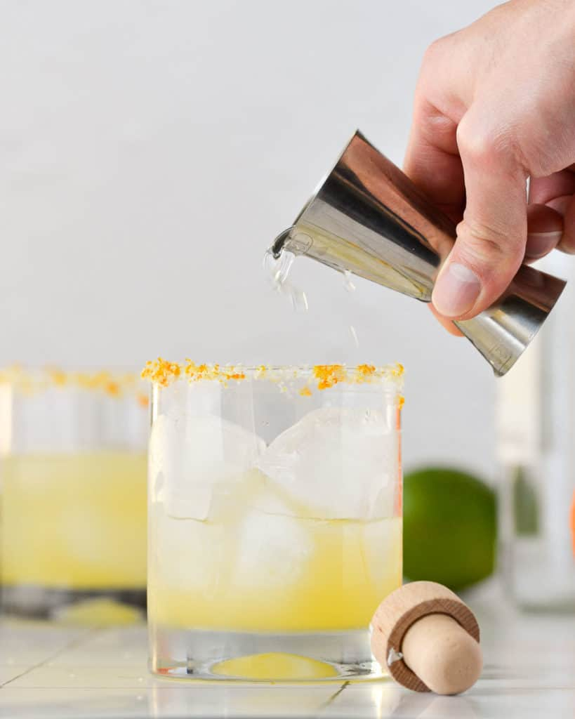 pouring tequila into a margarita glass
