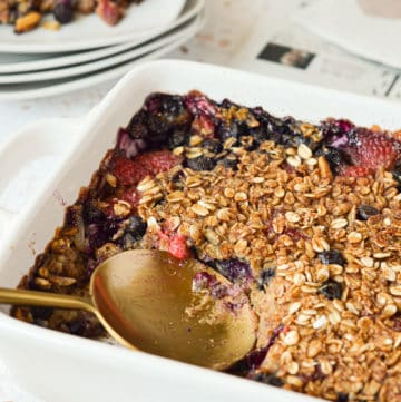 scoop and spoon in a baking dish of baked oatmeal with blueberries