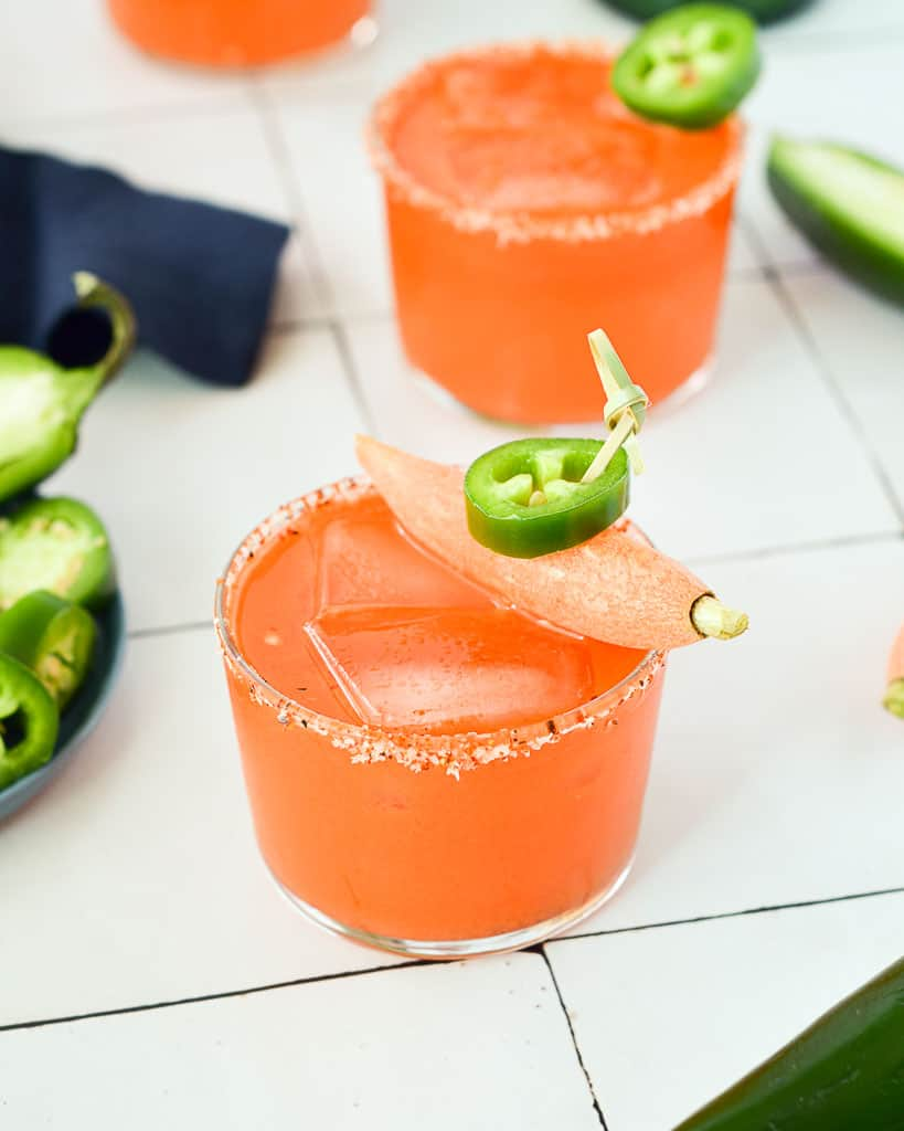 three carrot juice mezcal margaritas with a tray of jalapeños