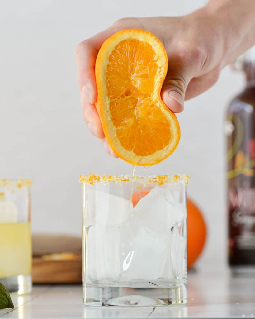 pouring orange into a skinny margarita with red wine sangria