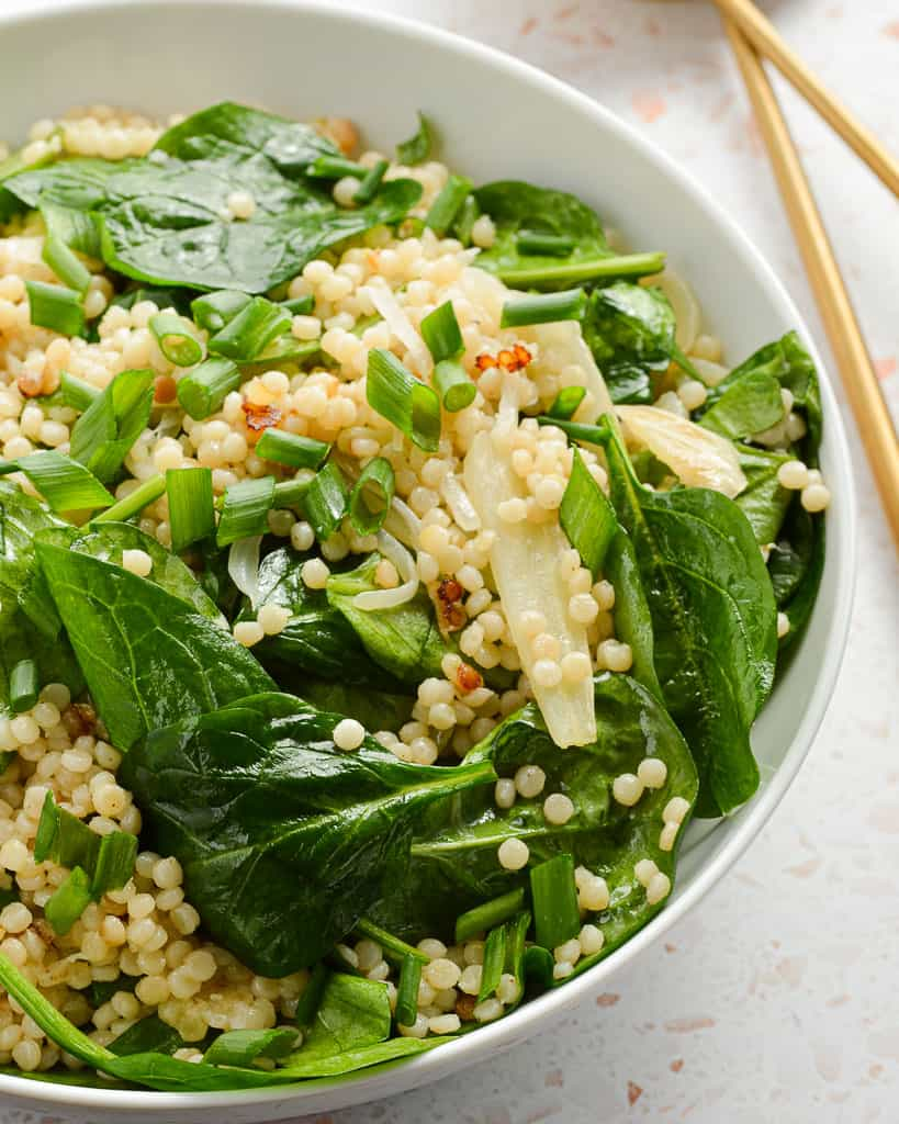 close up of an Israeli couscous salad with wilted spinach