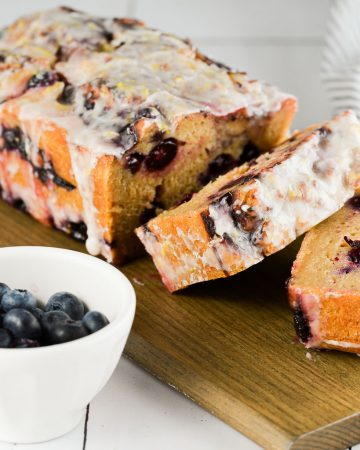 Lemon Blueberry Bread slices with fresh blueberries on the side