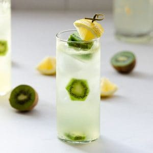 spiked vodka lemonade in a tall glass with a lime wedge and kiwis inside