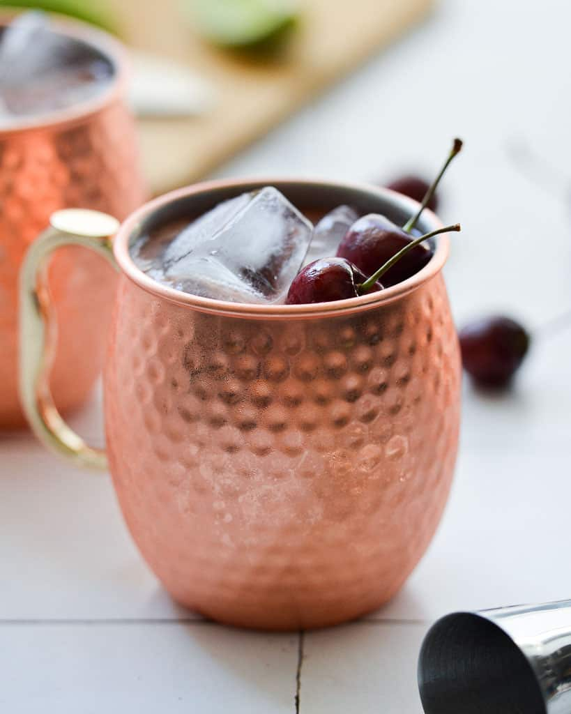 close up of a copper mug holding a moscow mule with cherries