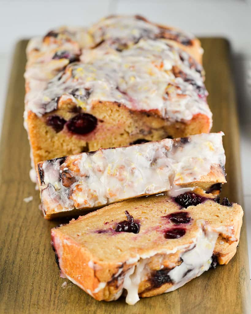 cooked lemon blueberry bread slices on a cutting board