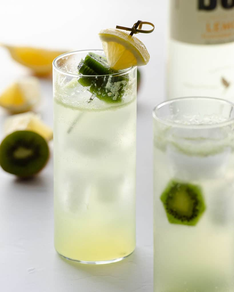 two spiked lemonade cocktails with kiwis