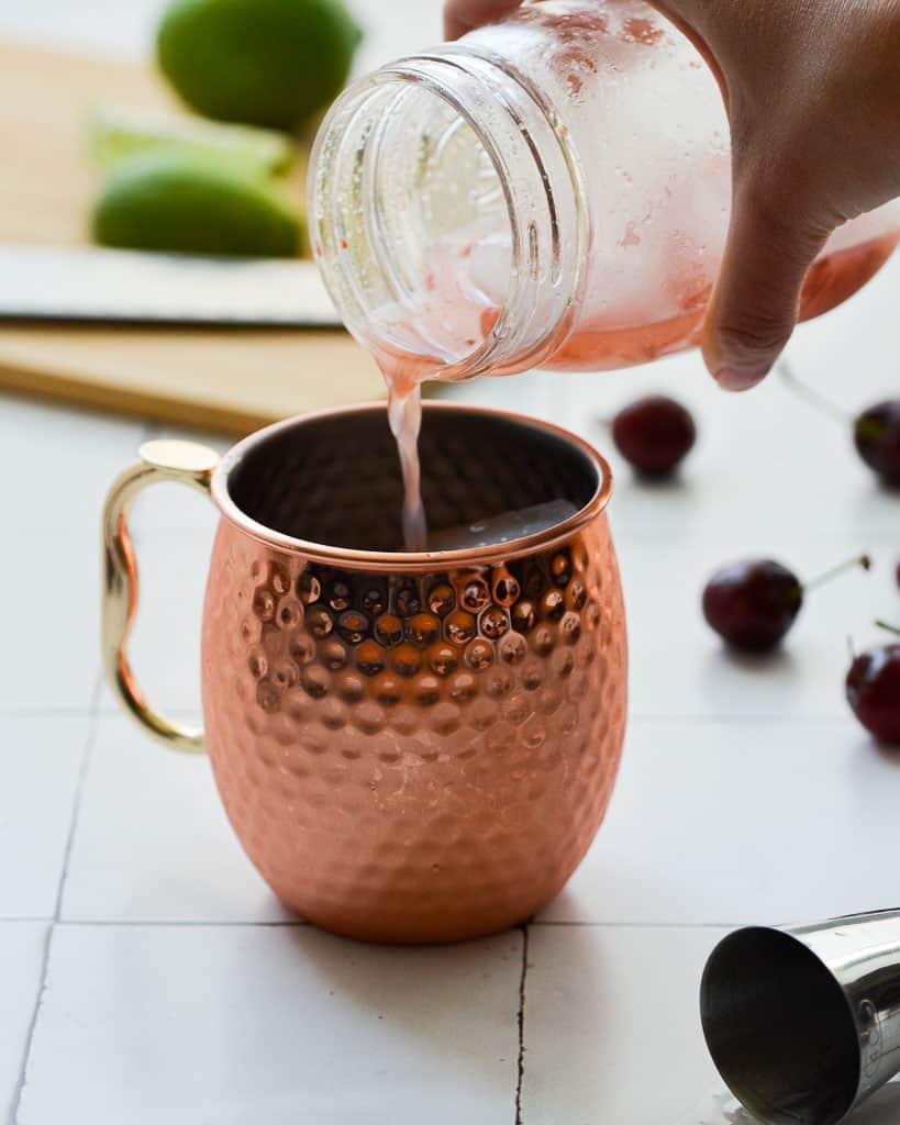 pouring vodka cherries into a copper mug