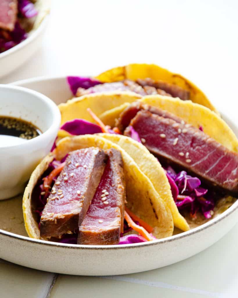 two slices of seared ahi tuna in a corn tortilla with cabbage and carrot and ponzu sauce on the side