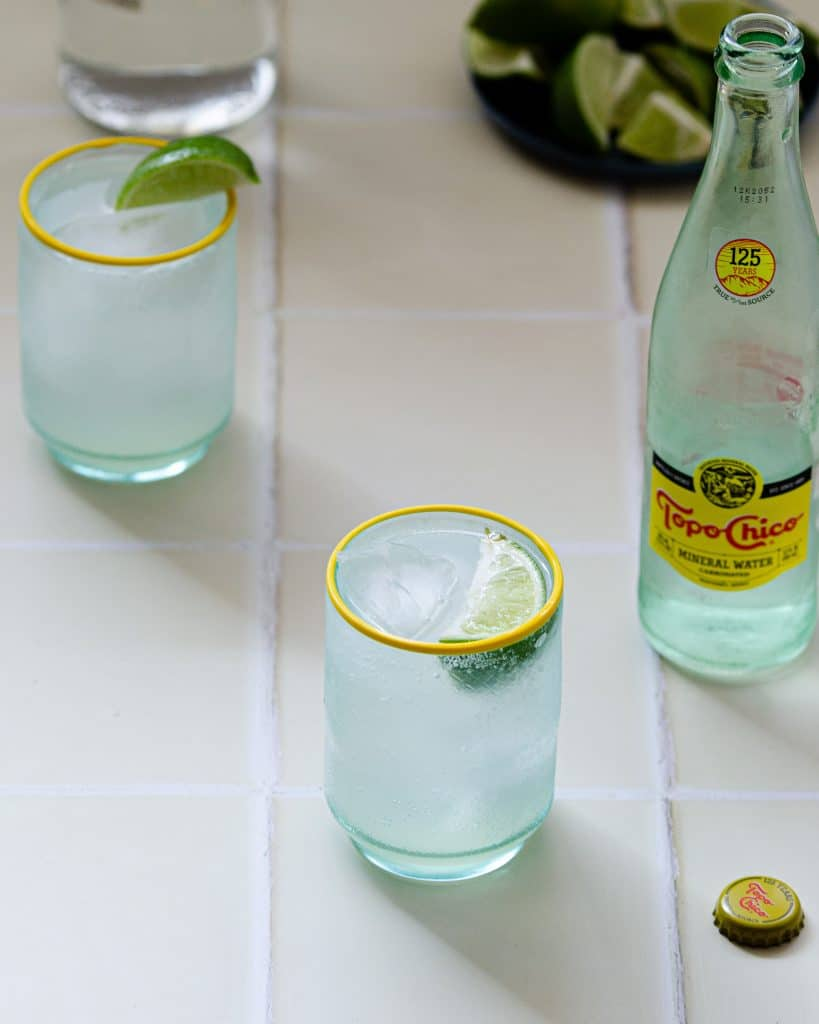 overhead of two ranch water cocktails with limes in the back and topo chico in the front