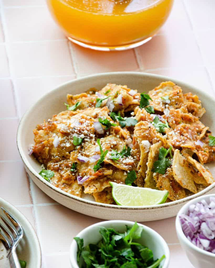 a plate of chilaquiles rojos with cilantro and red onion and orange agua fresca in the back