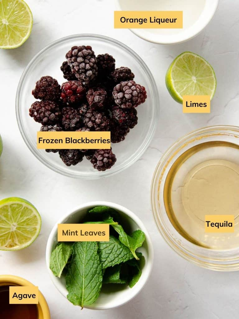 all of the ingredients in separate bowls: orange liqueur, frozen blackberries, limes, mint leaves, tequila and agave.