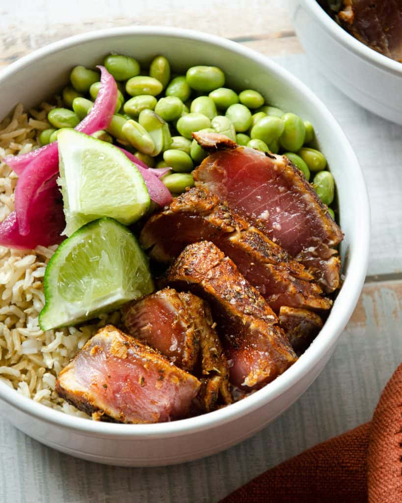 a white bowl with slices of seared ahi tuna, limes, pickled red onions and edamame over brown rice