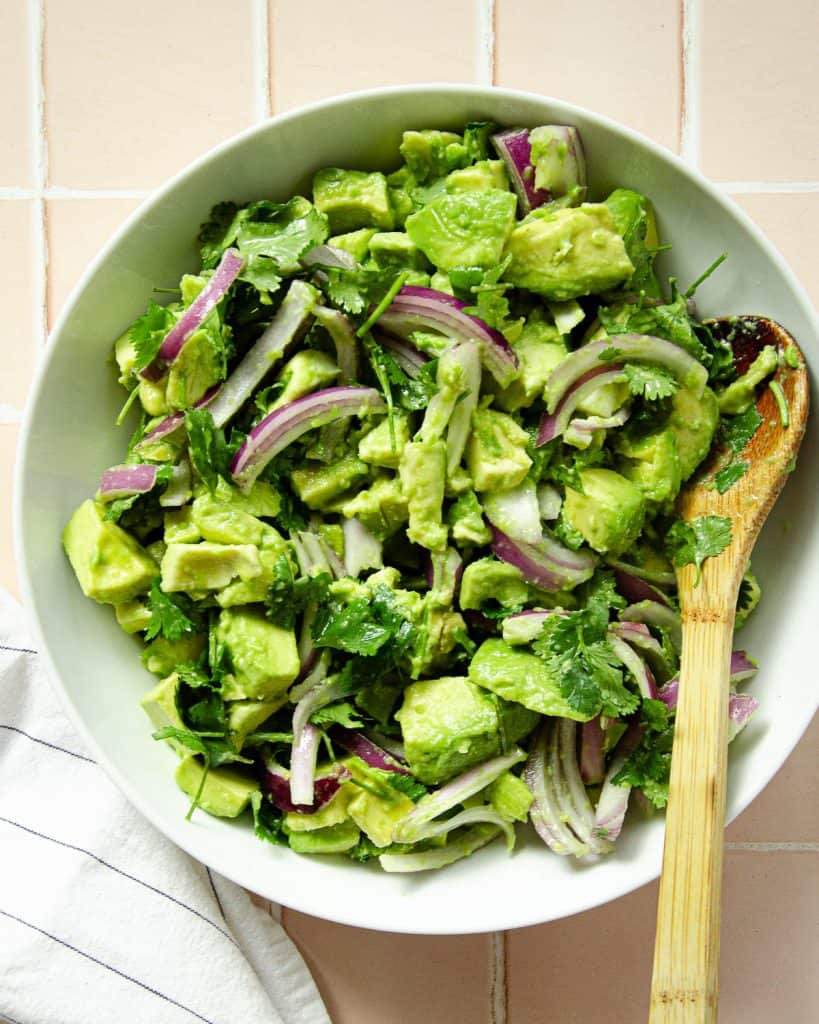 chunky avocado, red onion and cilantro in a large white bowl with a towel on the side and a wooden spoon inside.