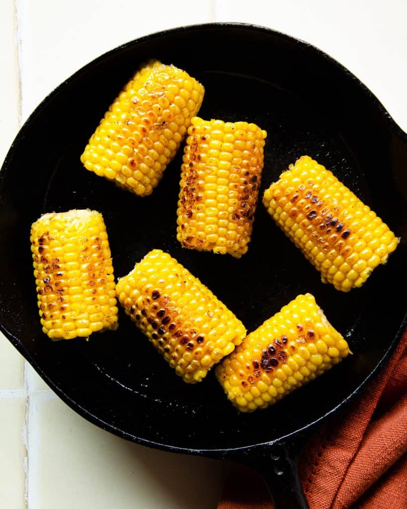 charred corn on the cob in a cast iron pan