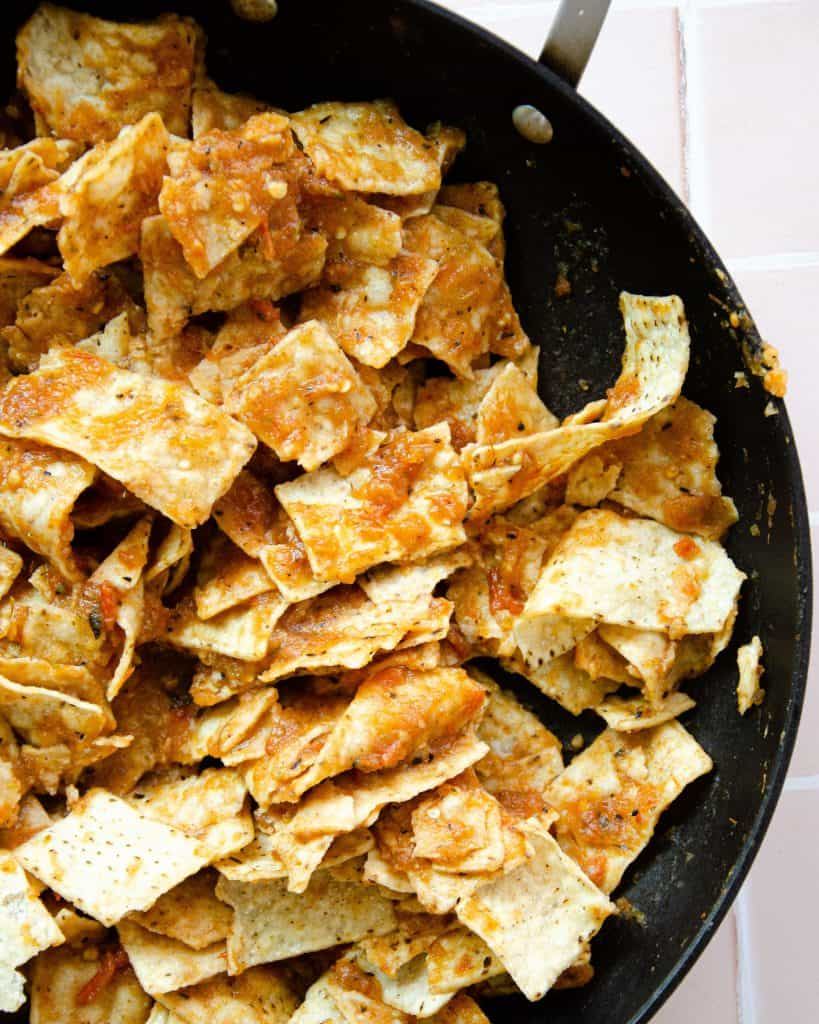 corn tortilla strips in a pan soaked in a red chilaquiles sauce