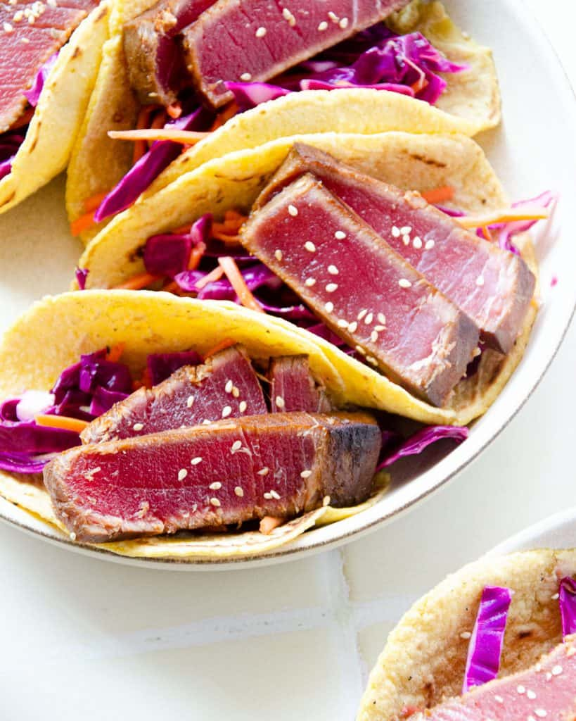 close up of seared tuna in corn tortillas with cabbage and carrot slaw underneath