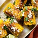 close up photo of corn on the cob with cotija cheese, cilantro and tajín