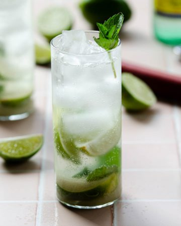 completed mocktail mojito in a tall glass with limes, a muddler and other glass in the background.