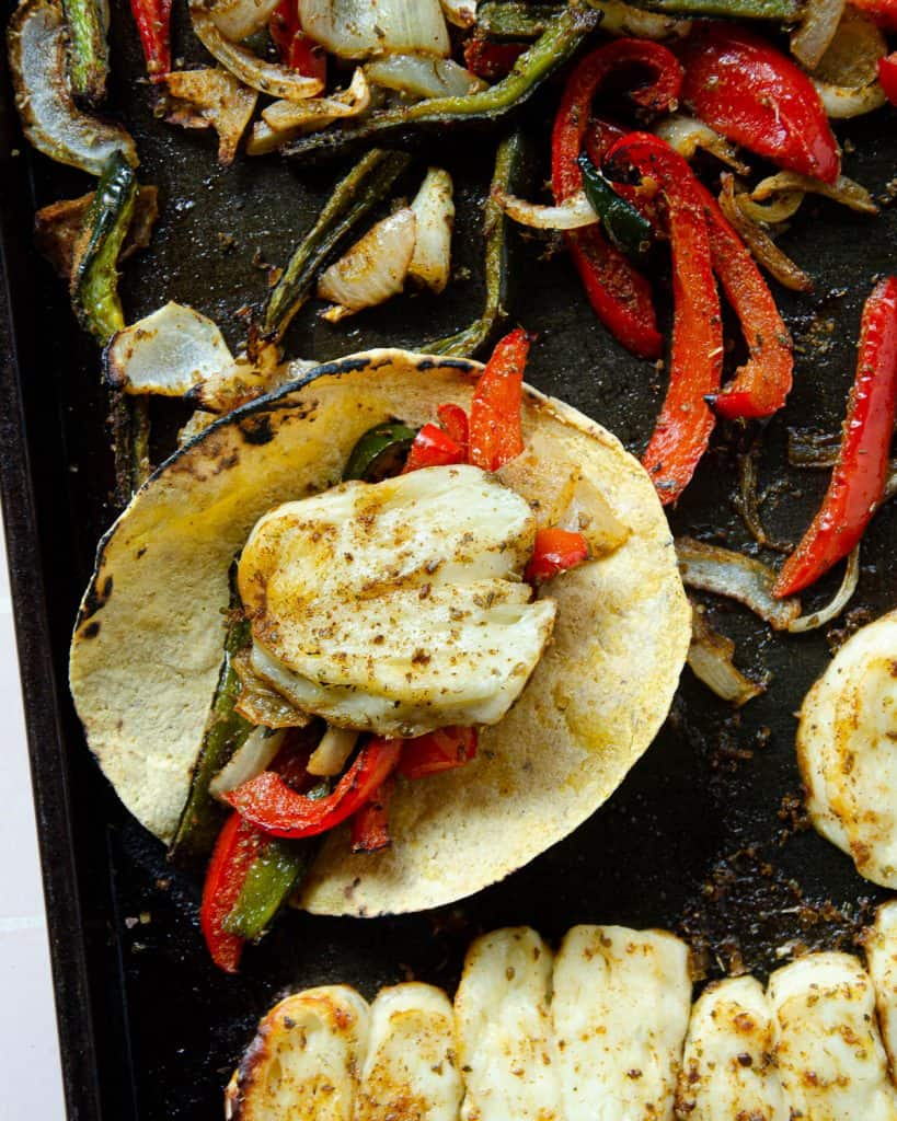 corn tortilla with halloumi, peppers and onions all on a sheet tray