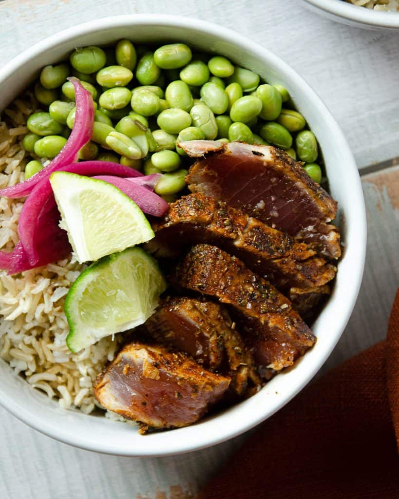 sliced and seared ahi tuna in a bowl with pickled red onions, lime and edamame