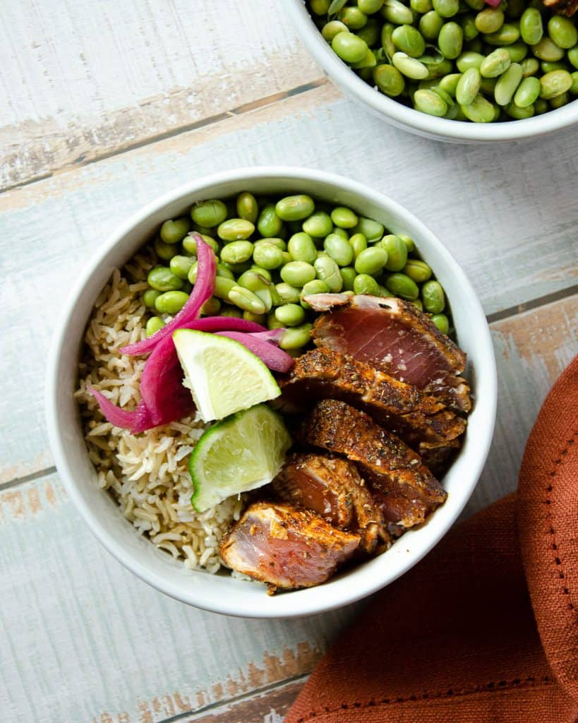 two bowls of ahi tuna siting on top of rice, edamame, and pickled red onion
