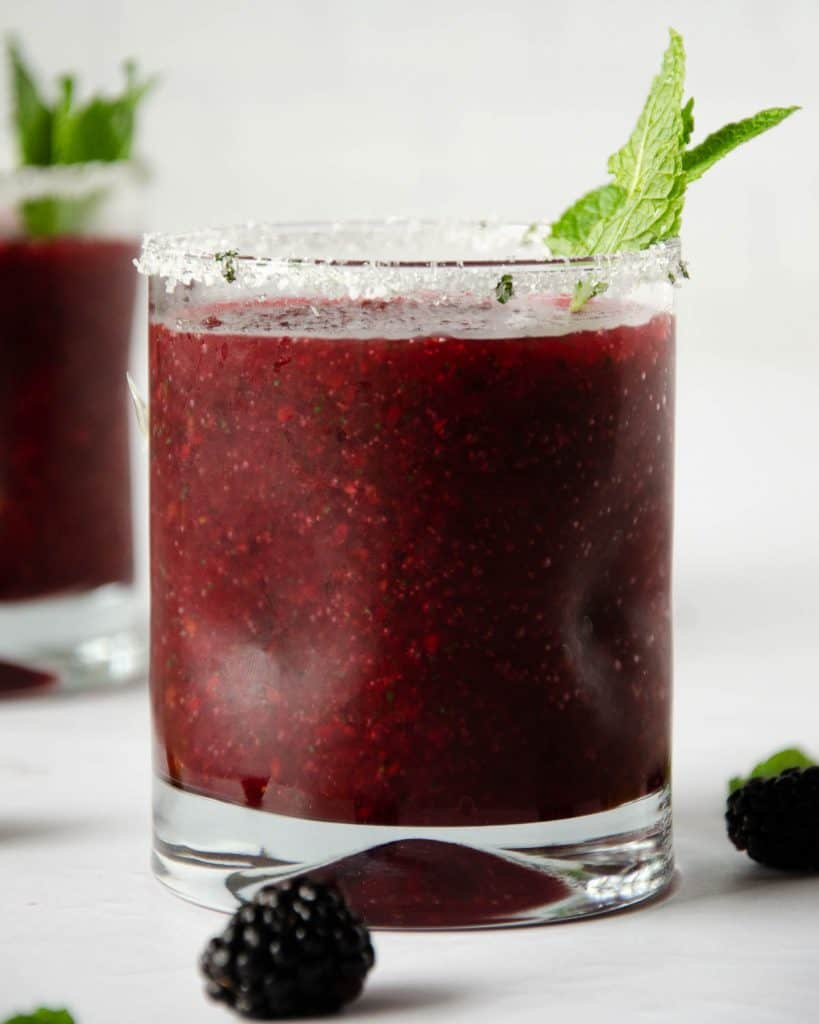 small glass filled with a frozen blackberry margarita with a mint leaf on top. frozen blackberry glass in the back left