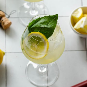 an overhead view of a limoncello spritz with lemons and a muddler underneath