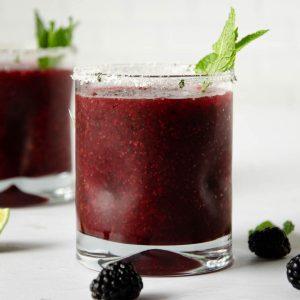 frozen blackberry margarita with mint inside it.