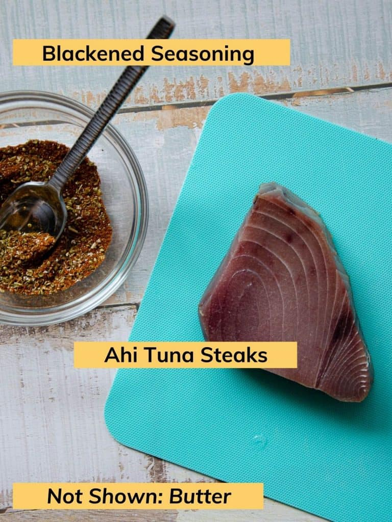 an ahi tuna steak on top of a blue cutting board and a bowl of blackened seasoning