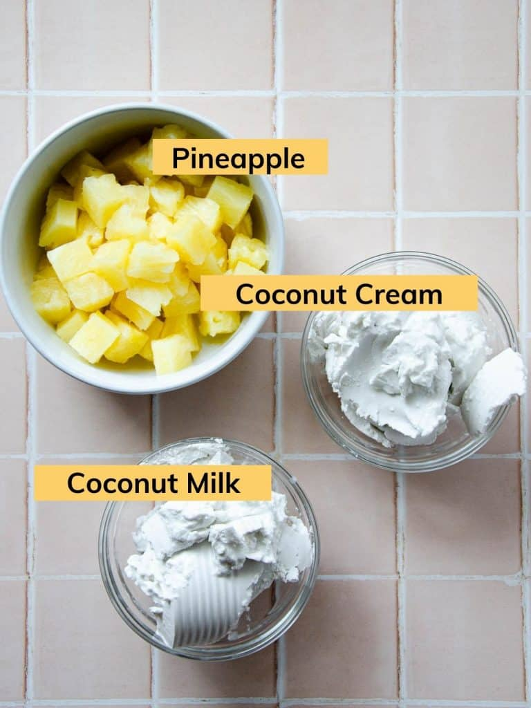 a bowl of pineapple chunks, a bowl of coconut cream and a bowl of coconut milk
