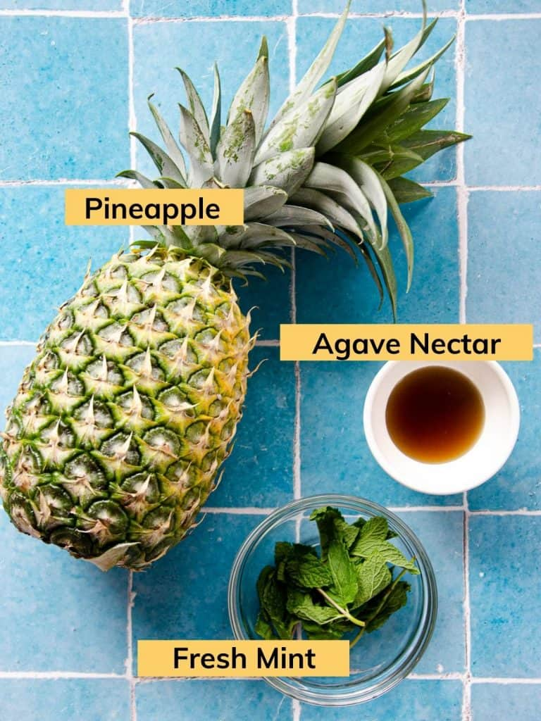 a whole pineapple, a bowl of fresh mint and a bowl of agave nectar on tile