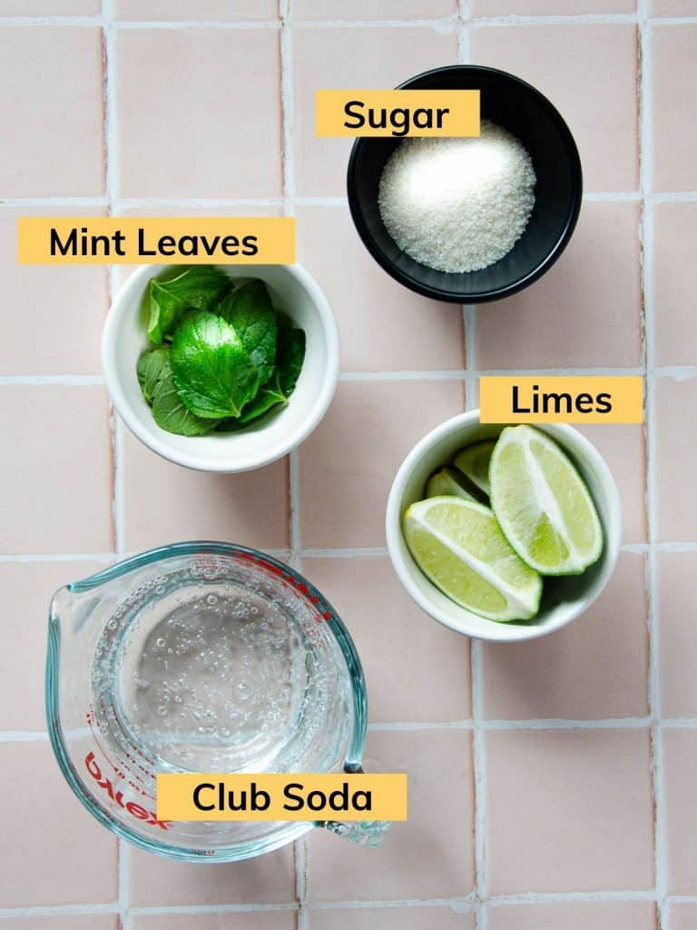 bowl of lime wedges, bowl of fresh mint leaves, a bowl of sugar and a pyrex glass of club soda.