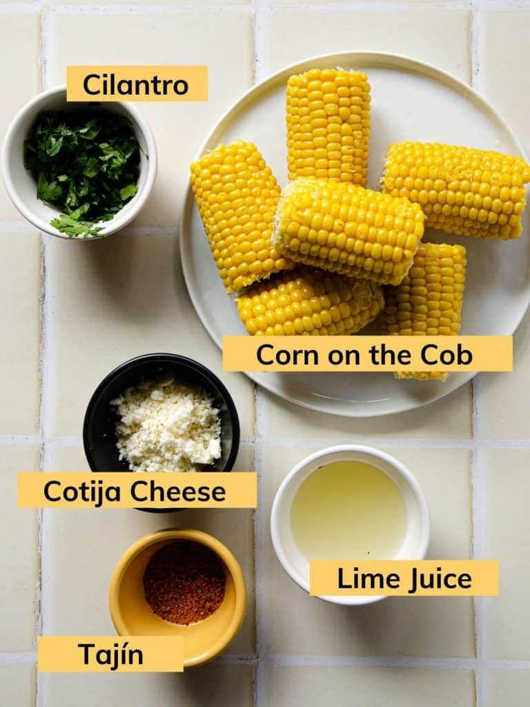 corn on the cob, chopped cilantro, cotija cheese, lime juice and tajín in bowls on the counter