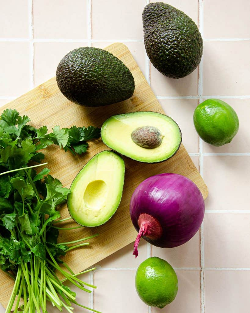 ingredients laid out on top of a cutting board: split open avocado, cilantro, limes and a red onion