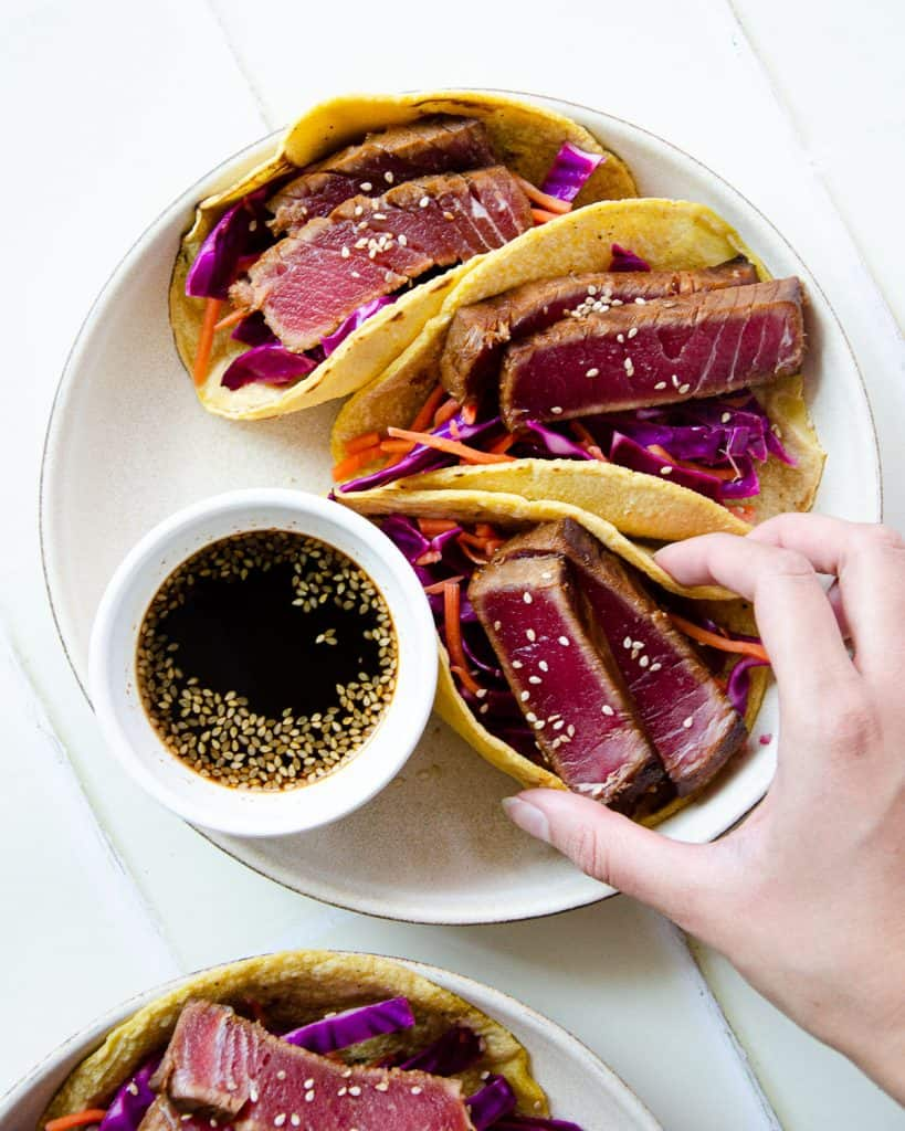 hand grabbing a ahi tuna taco from a plate of three