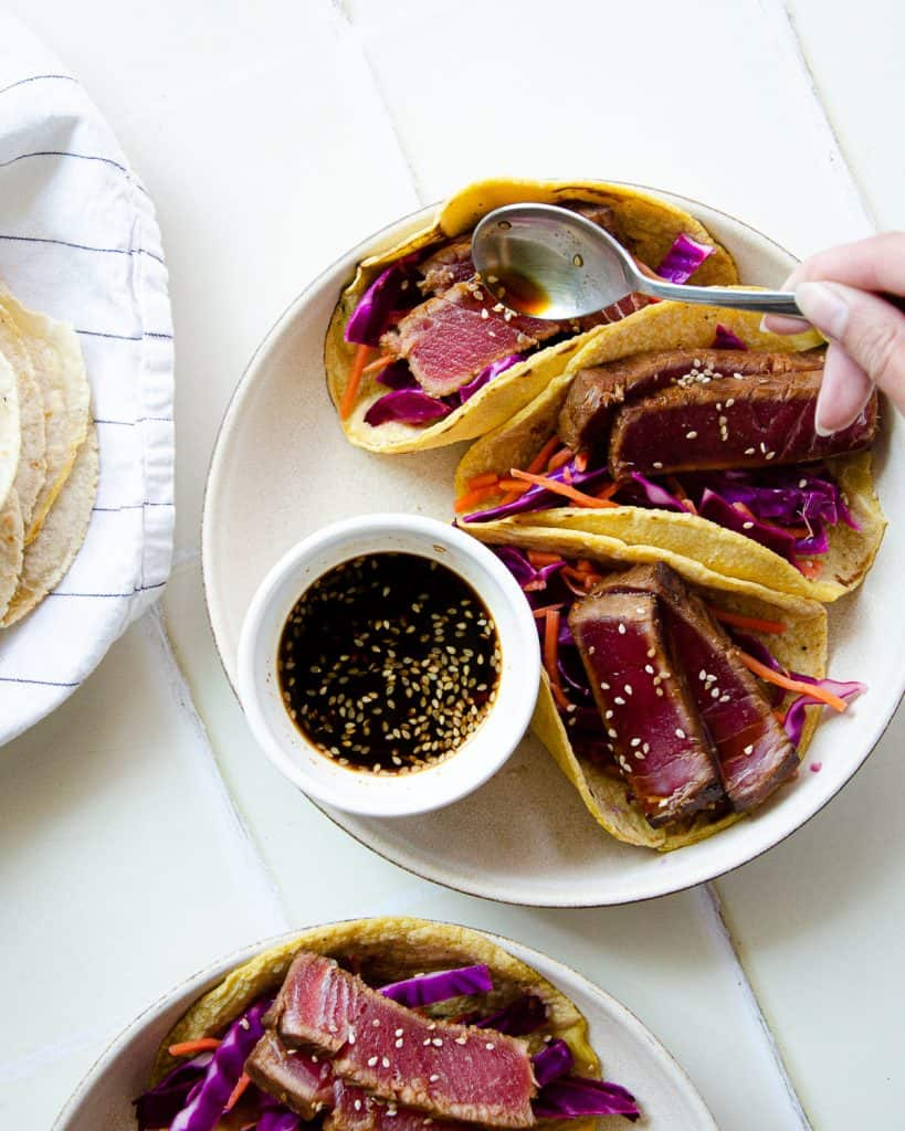 pouring ponzu sauce over a plate of three seared ahi tuna tacos