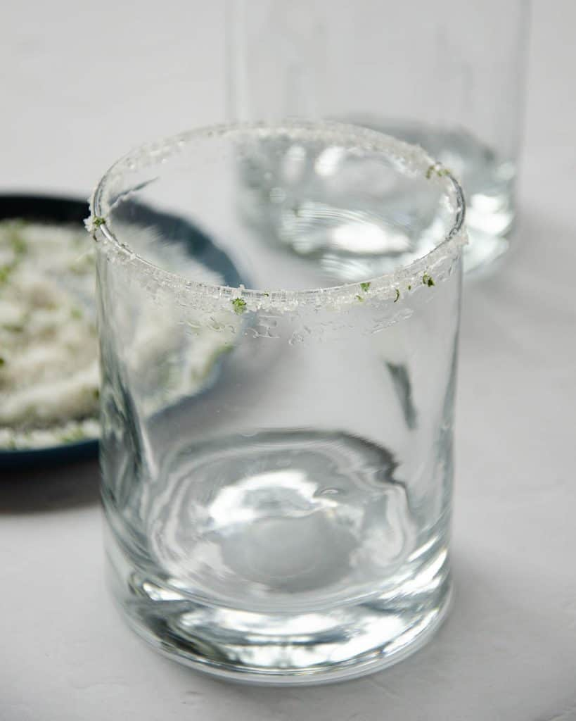 sugar salt and chopped mint on the rim of a glass with a blue plate with sugar and mint on the left.