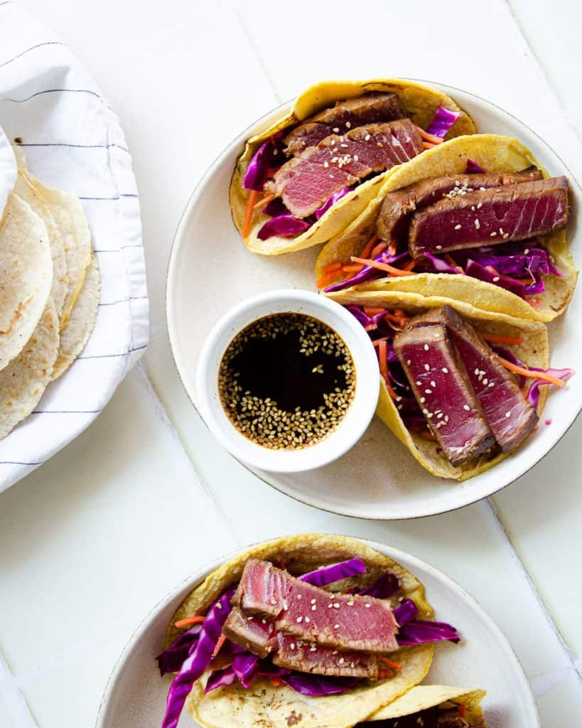 two plates of ahi tuna tacos with ponzu sauce and corn tortillas wrapped in towels on the side