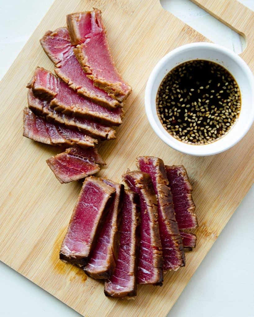 sliced and seared ahi tuna steaks on a cutting board with ponzu sauce