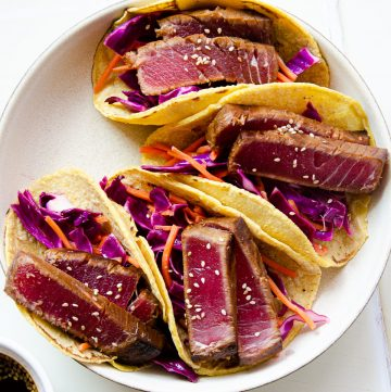 Close up of a plate of four seared ahi tuna tacos on top of a cabbage and carrot slaw