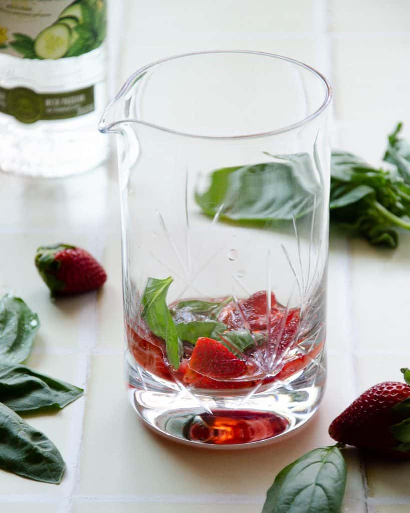 muddle strawberries and basil leaves in a crystal glass